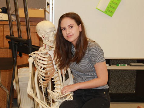 """Junior Hampton Williams poses with a skeleton during her independent study, which she spends in room 552. Williams said she doesn't care about what people think about heer clothing. """"I only dress for myself and I do it because I think it's one of the most expressive forms of art that anyone can do — everything you put on everyday is a statement,"""" she said."""