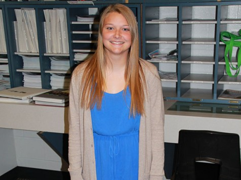 """Sophomore Taylor Holtmeyer poses in a blue dress and cream-colored cardigan. She said she always finds a way to put blue into her outfit. """"Blue is my favorite color, I love to wear it because it matches my eyes,"""" she said."""