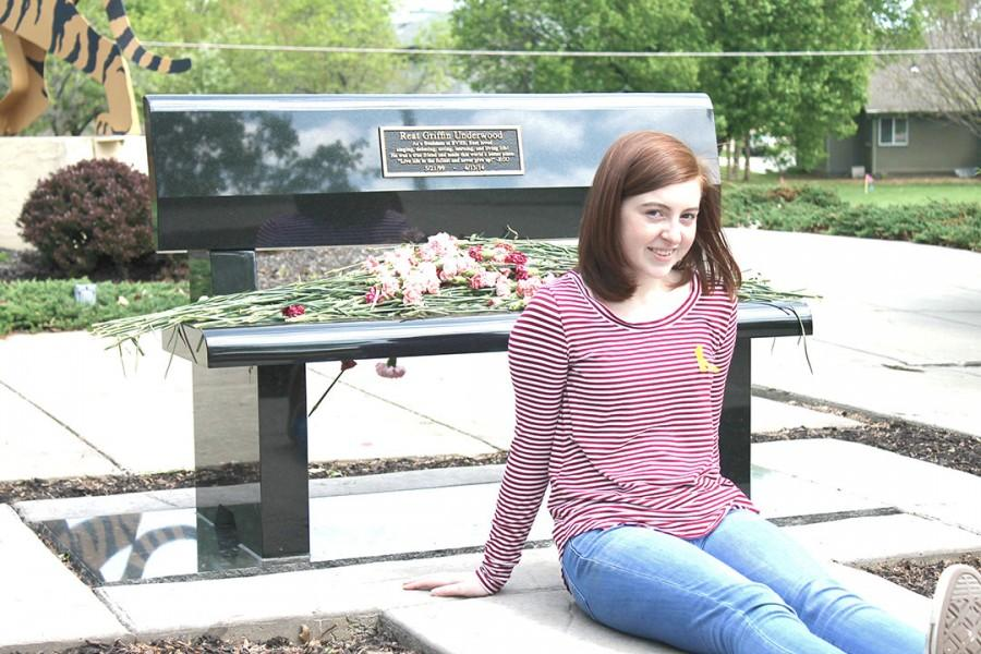 "Cotter-Brown sits by the Reat Underwood Memorial bench in front of the school. ""Everything that has happened has created community — in this school and in this area,"" Cotter-Brown said."