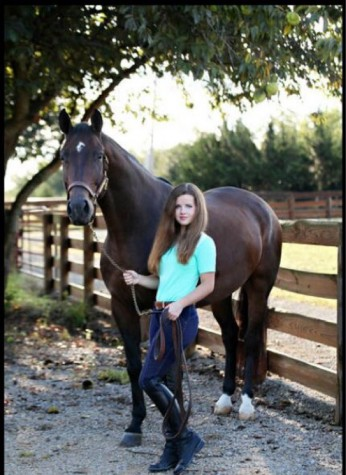 "Senior Alexis Vance is standing by her strongest companion, and best friend, Encore. Vance has been riding for over ten years now, and is ready to follow through with her lifelong ambitions. ""Life is like a horse"" Vance said. ""If it tries to buck you off, just hold on a little tighter."" Photo by Loren Reed"