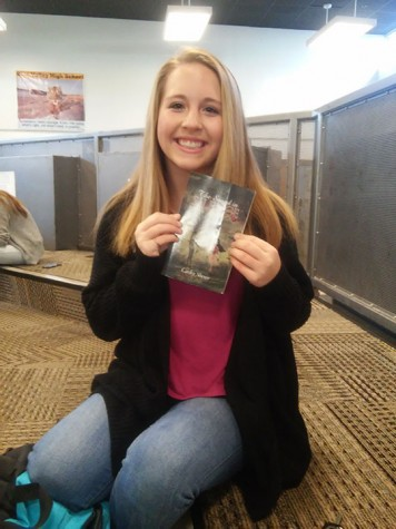 "Sophomore Carley Sherer holding up her book ""The Sound in Silence"" in the fixed forum."