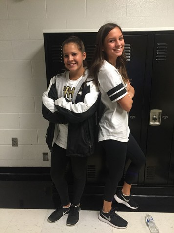 """Sophomore twins, Anna and Abby Quigley, pose back to back in the halls of Blue Valley. The Quigley's both participate in cheer at the school and are shown wearing spirit wear. """"Cheer is one of the many things we enjoy doing together,"""" Anna said. Photo credited to Emma Andersen."""