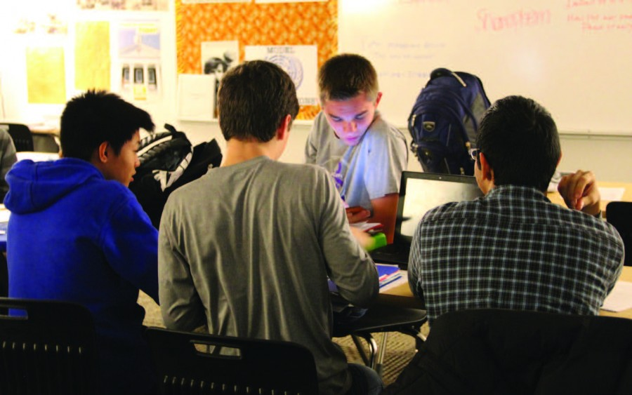 """Researching on his phone, sophomore Christian Hansen converses with other Model UN members. Hansen is the president of the club. """"[Model UN] is different because it is the only activity which requires you to take the positions of another country and make them into your own,"""" he said. Photo by Isabelle Allen."""