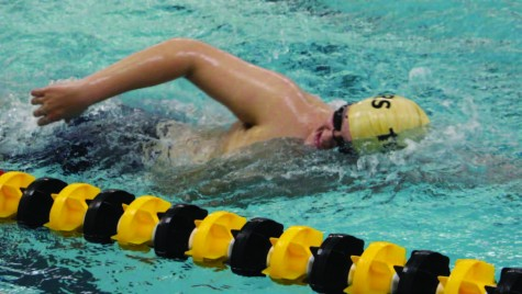 """For his warm-up, senior Adam Houghton swims freestyle. The swim team practice 10 times per week, both before and after school. """"It's a lot of muscle memory,"""" he said. """"If you do it repeatedly, you get better at it."""""""