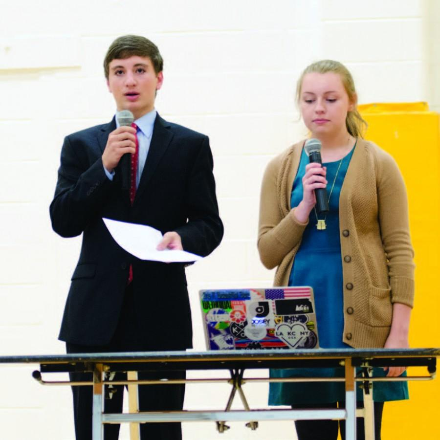 "Senior Amanda Miller cross-examines sophomore Louis Pires at the Fine Arts Potpourri. Each year, debate students perform a mock debate at this event. ""Debate creates a community of learning that is beyond what we get at school,"" Miller said. ""It encourages us to be more aware of what is going on in the world and to discuss it."" Photo by Maddie Davis."