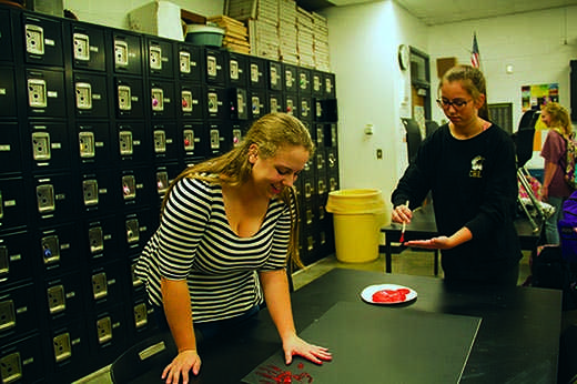 """Junior Sydney Van Ophem presses her handprint on a poster. National French Honor Society met Nov. 19 in one of the art rooms. """"NFHS is sending [the handprint chain and poster] we made to a school in Paris to show support after the attacks,"""" Van Ophem said."""