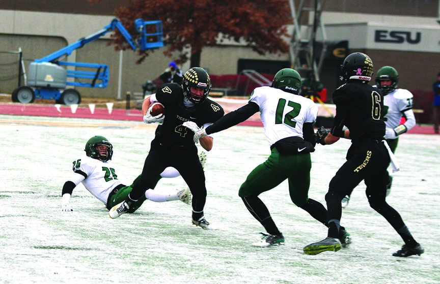 """After catching a pass, senior Taylor DeBey runs the football during the State championship. Due to two days of rain and sleet before the game, the field was frozen. """"It was definitely hard to make some cuts and move around,"""" he said. """"It was just as bad as it looked."""""""