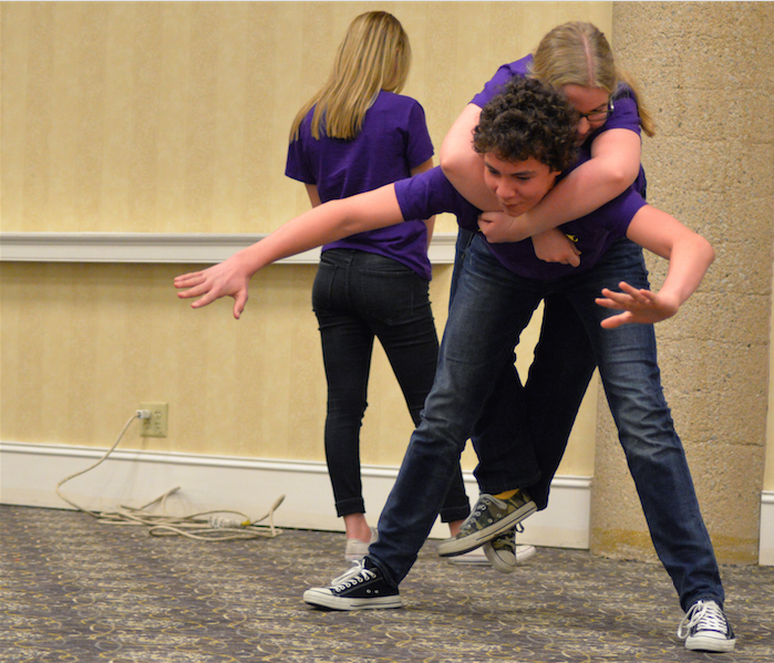 Getting his balance, sophomore Garrett Gunnerson holds junior Lorna Hurt on his back. Drama teacher Jeff Yarnell lead the improv competition at the conference.