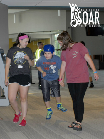 """Senior Amy Reglin walks with her buddy down the hallway to another activity at a SOAR R&R night. Reglin said she loves to spend time with the kids and get to know them better at the R&R nights. """"We get to hang out with the kids when it is not structured. If a kid wants to sit and play with sand the whole night, he can do that,"""" said Reglin."""