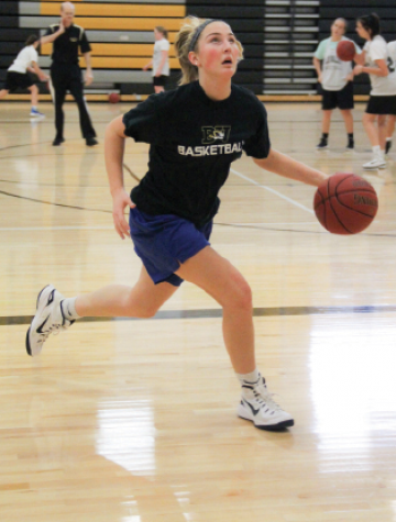 "Dribbling the ball, junior Katie Beth Jones runs down the court. Jones has played on varsity since her freshman year. ""We had a lot of senior leaders last year, so the juniors are going to need to take it upon ourselves to lead the team more,"" she said."
