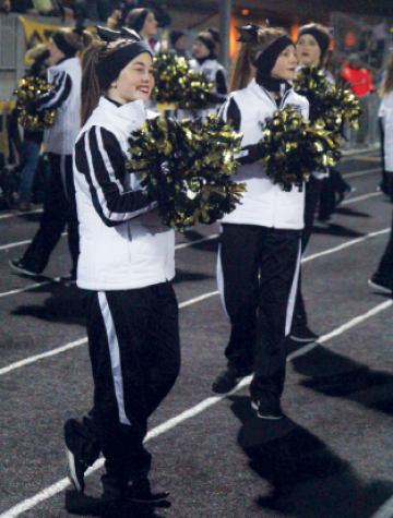 "Freshman Brooke Erdley cheers on the football team during the Substate game against Shawnee Mission East on Nov. 18, which went into overtime. The dance team performed on the sideline at home football games. ""I like the experience of performing at school events because it's more fun and laid back,"" Erdley said."