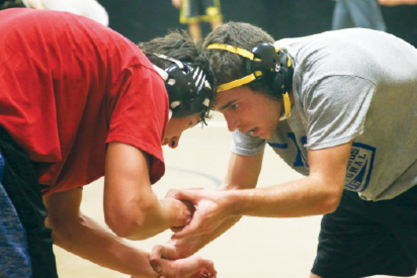 """Facing his opponent, junior Grant Boehringer assumes neutral power position. You can score points in wrestling with a take-down or escape. """"I love the competition and grit necessary to wrestle,"""" he said."""
