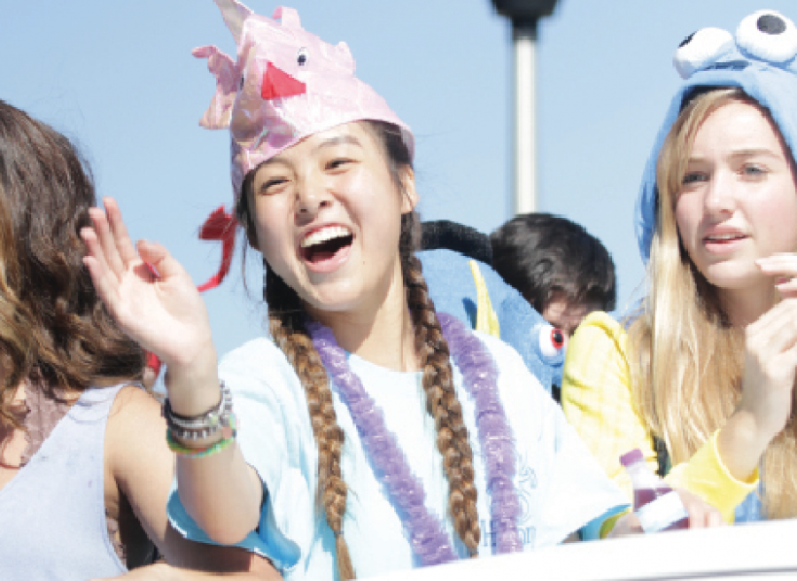"""Sophomore Student Council representative Angie Yu waves to the crowd. The parade was Sept. 30. """"Whenever we had to work together [on the float,] it was a lot of work especially since it was a small float,"""" Yu said. """"I liked figuring everything out and seeing it all come together."""" Photo by Isabelle Allen."""