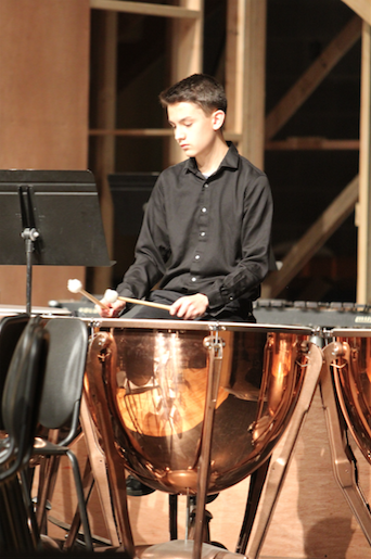 """Reading his music, freshman Owen Bienz plays in the Spaghetti Concert. Bienz is in Concert Band, which is directed by Carol Lowman. """"I have been playing drums since fifth grade,"""" Bienz said. """"[Band] is fun, and there is a lot of people that like the stuff I do."""" Photo by Isabelle Allen."""