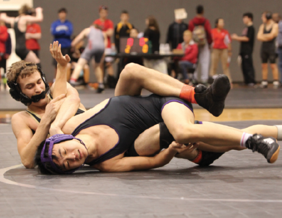 """Laying on the mat, freshman Jake Hutchison attempts to pin his opponent. Hutchison has been wrestling for three years. """"I started wrestling because I liked the idea of having a sport that sixth graders could do,"""" he said."""