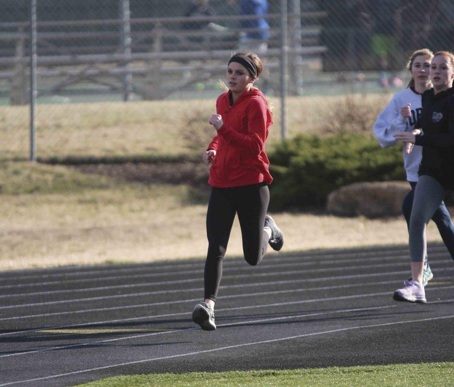 "Sprinting down the track, junior Abby Quigley trains during practice. Quigley has been competing at the varsity level since her freshman year. ""I am looking forward to all that we can accomplish this season,""  she said."