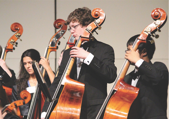 """In the PAC, sophomore Tyler Gerry plays at a concert with the orchestra. The BV orchestra is conducted by Amy Fear. """"My favorite part is the people,"""" Gerry said. """"[I have played] the base since elementary school."""""""