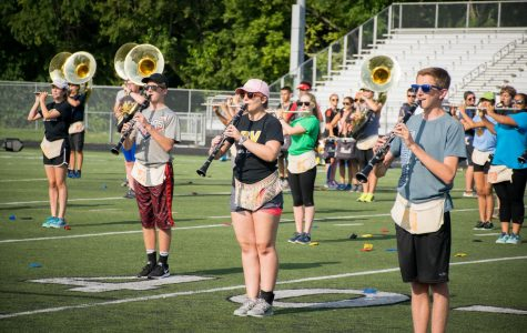 """Standing in place, senior Madison Ashworth plays the flute with her bandmates. """"Rehearsing is worth it because you are contributing to something that is so much more than you. You are just one dot in a huge picture,"""" she said."""