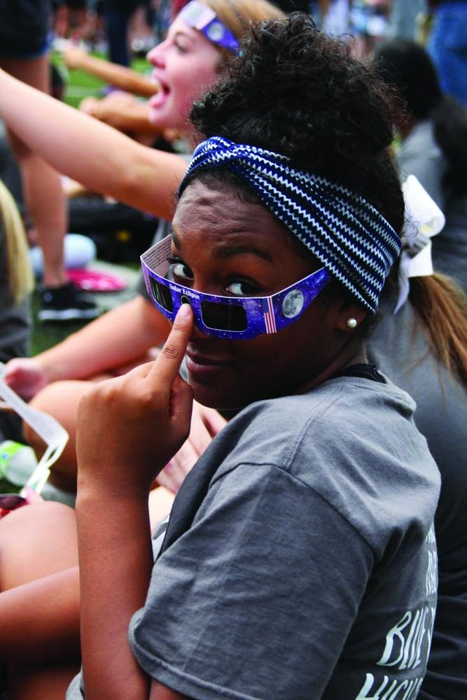 """Showing off her eclipse glasses, junior Shanyn Longsworth sits among her friends. """"I was really excited, but it turned out to be a bummer."""""""