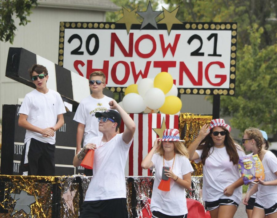 """Fist pumping, freshman Grayson Edmonds participates in the Homecoming parade. """" I built some of [the float] on a couple of Saturdays and painted it, too,"""" he said."""