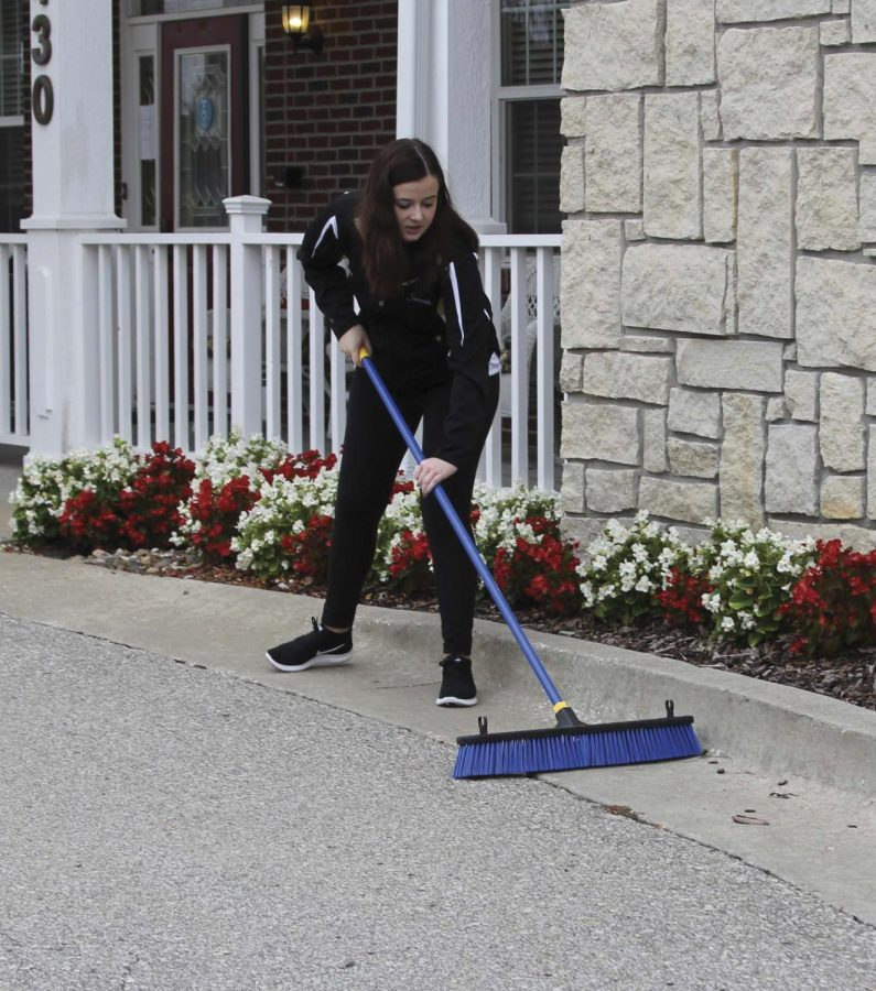 """Sweeping a driveway, senior Jessica Justmann volunteers at Vintage Park. """"My most meaningful experience was talking in Spanish to a woman from Peru,"""" she said. """"It made me realize how little world experience I have."""""""