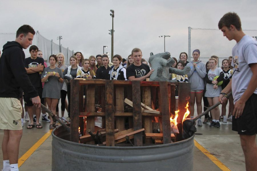 """Senior Nick Lester throws the BV Southwest Timberwolf on the fire. Students in National Art Honor Society created the Timberwolf. """"[This] is a great way to get everyone excited for the homecoming game,"""" Lester said."""