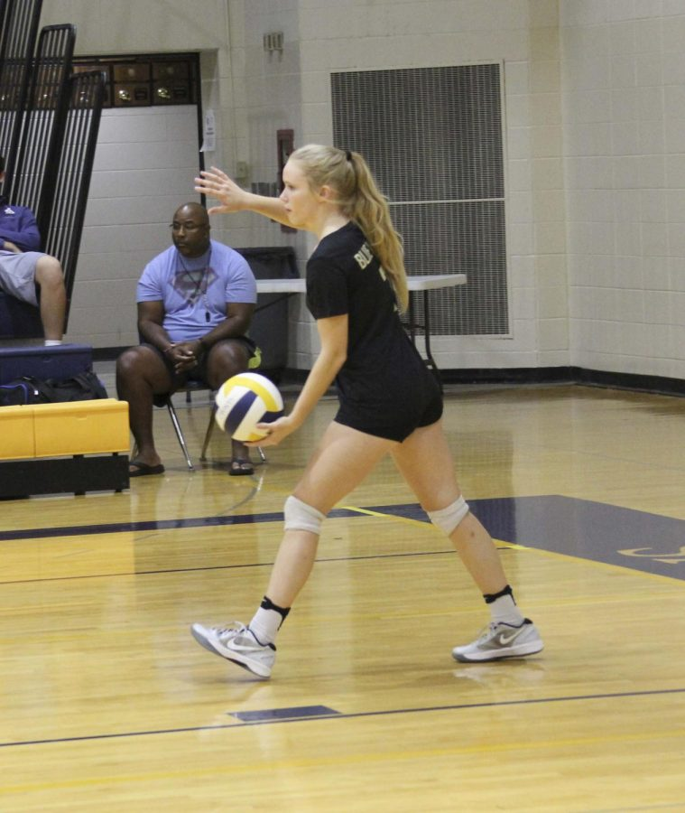 "Preparing to serve, sophomore Taylor Daurenheim competes in a match. ""We're all like family,"" she said ""We're really close on and off the court."""