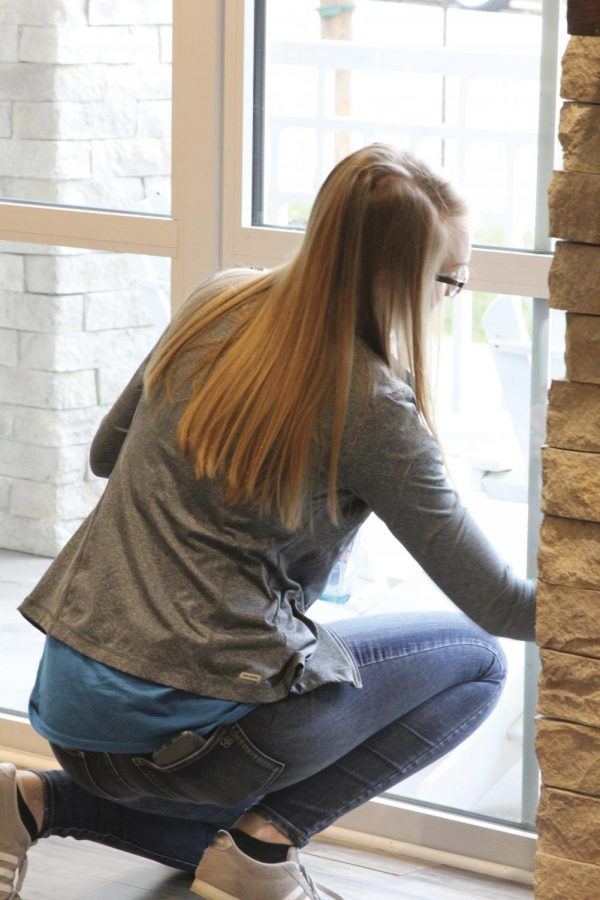 """Scrubbing a window, senior Lily Cordes volunteers at the Ronald McDonald House. """"We helped with a lot of housekeeping stuff, """" she said. """"My favorite part was getting to see the volunteers help Ronald McDonald out. It was a really rewarding experience."""""""