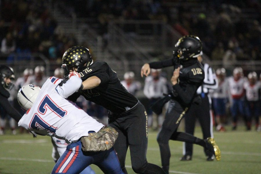 The Olathe North defense is held off as senior Luke Bernard attempts to complete a pass. The Tigers won 48-21 and claimed the title Sectional Champions.