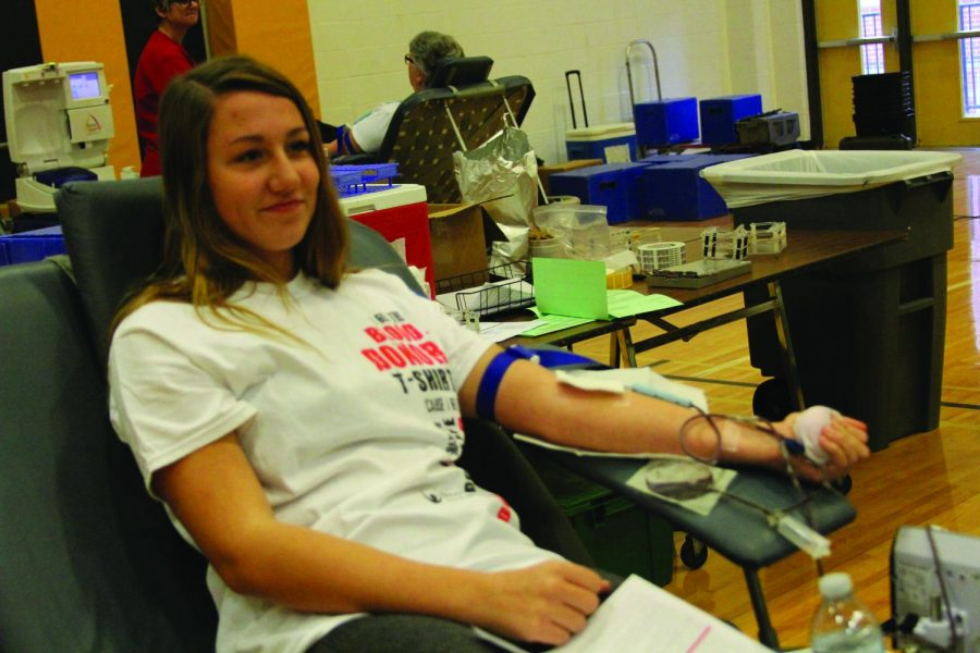 """Giving blood, junior Bailey Sibenaller donates in the auxillary gym. """"[Giving blood] is very important to the people who need it,"""" she said. """"[I wanted] to give back to the community."""""""
