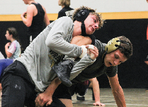 """Wrestling a teammate, senior Ben Mullinnix resists being pinned by junior Ethan Meuret. """"[I have the] responsibility as an upperclassmen to encourage the others and keep them motivated throughout the season,"""" he said."""