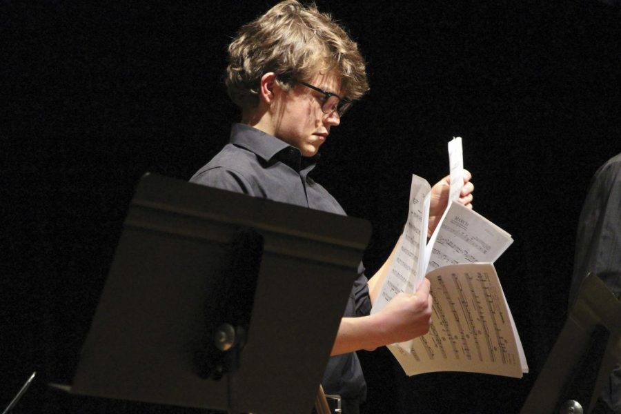 """Looking through sheets of music, junior Hamilton Brown switches songs during the Blue Valley Band's spaghetti concert, which entices eighth graders to join the band. """"I have a lot of friends in band,"""" he said. """"We all work really hard over the season to put out a good show."""""""