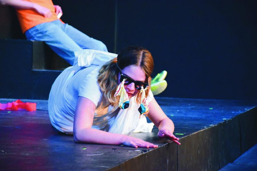 """Having just popped her eyes, senior Cat Simmons crawls on the floor during """"The Distracted Scholar's Guide to Literature and Drama."""" """"One of my favorite parts [about Rep Theatre] is being able to work on things in class,"""" she said."""