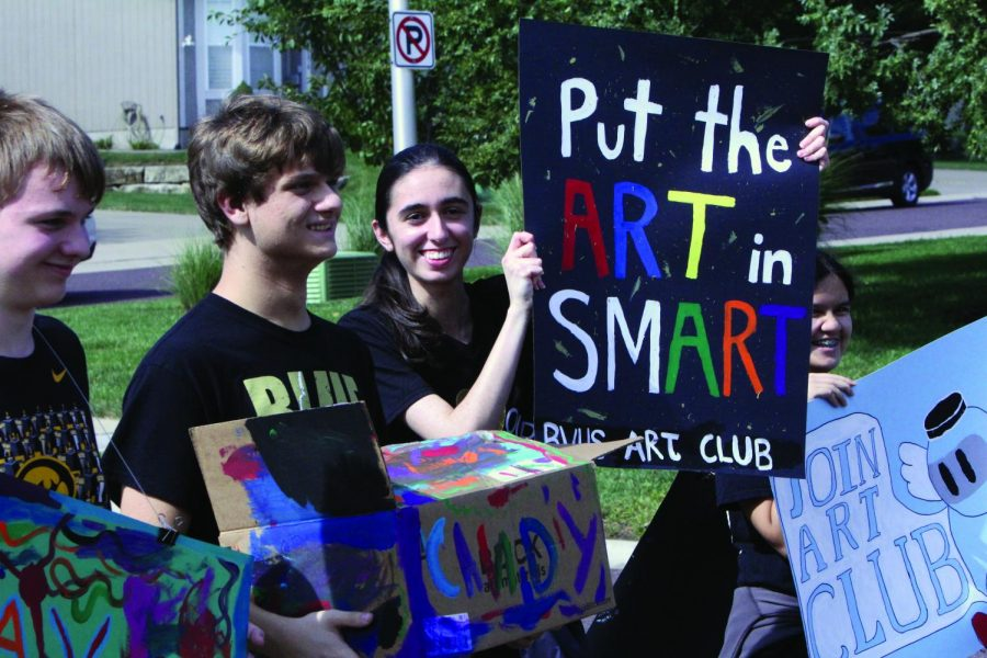 """Holding up a sign, senior Neeka Morelli walks in the Homecoming parade with Art Club. """"It was really special to me since I'm a senior and this is my last year,"""" Morelli said. """"I've been in the parade all four years."""""""