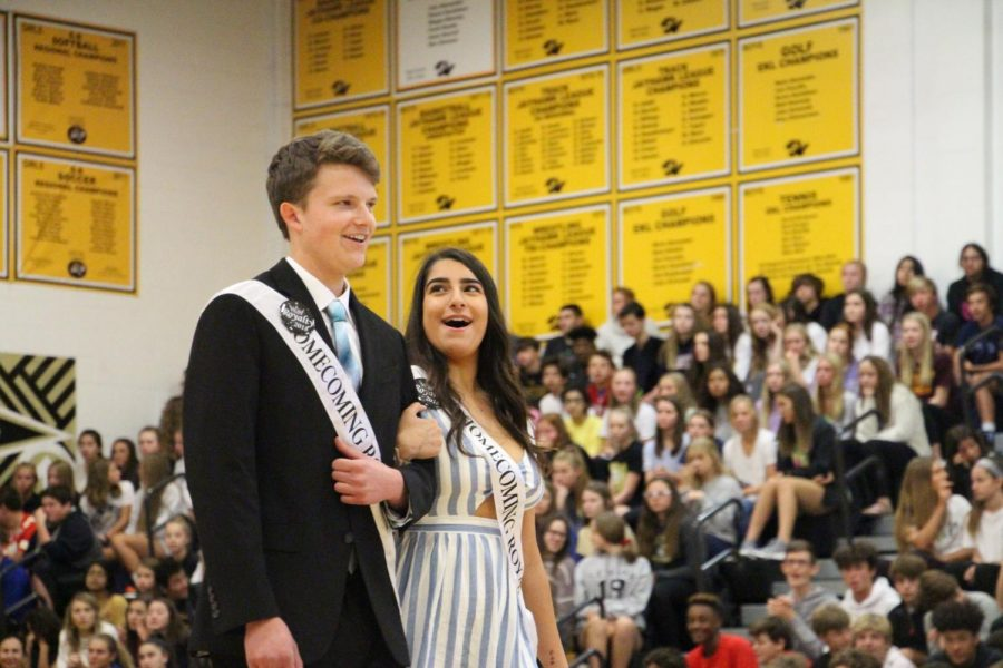 "Smiling to the student body, seniors Curran Whited and Ellen Nangia walk as Homecoming royalty at the assembly. ""I didn't expect to be nominated,"" Whited said. ""It was nice of people to vote for me."""