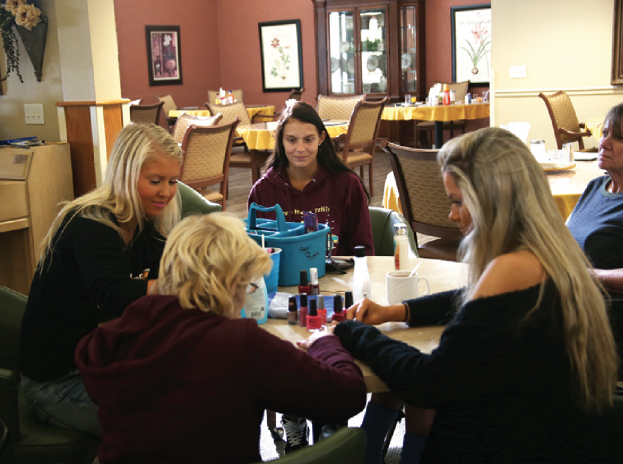 """Volunteering at Vintage Park, seniors Sheridan Hoy, Bella Bade and Ella Ciochon paint an elder's nails. """"My favorite part was just getting to know them,"""" Bade said. """"I loved watching how much they enjoyed the attention and company."""""""