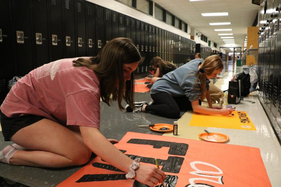 Getting ready to decorate the freshman hallway, freshman Leah Dunton paints signs.