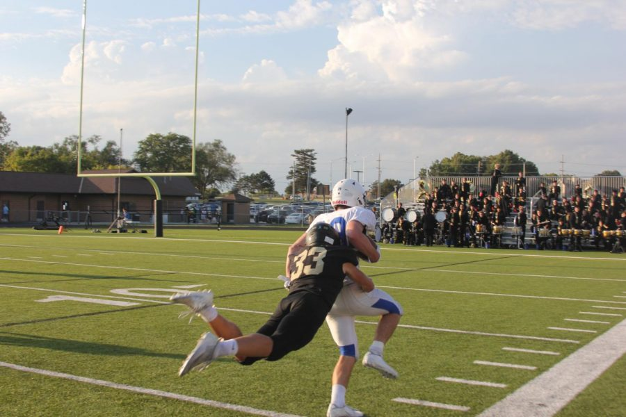 Caden McCumber tackles Rockhurst player to stop a touchdown.