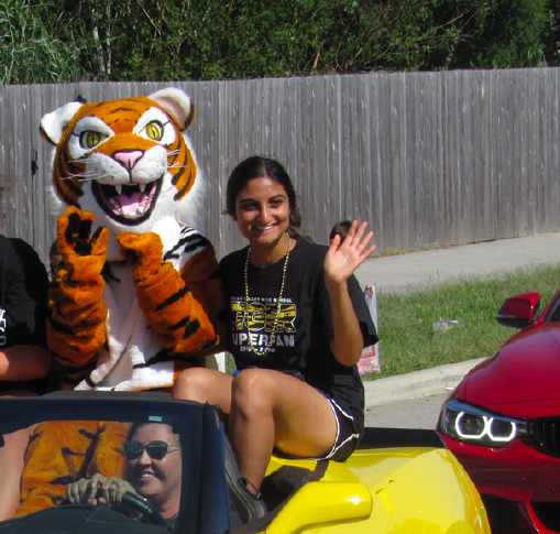 "Riding in the Homecoming parade, student body president senior Surina Walia waves to the crowd. ""We got to do a lot of new things that haven't been done at the school,"" she said. ""The most exciting part was incorporating all the other feeder schools."""